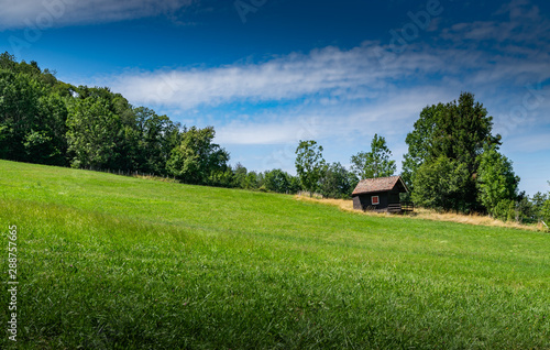 Valokuva View of a small wooden house on a mountain slope with a green meadow and the blue sky with white clouds,focus plane on the cottage