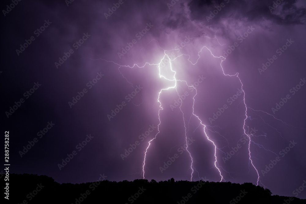 Fototapeta Lightnings over a forest during night thunderstorm