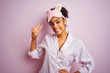 Young african american woman wearing pajama and mask over isolated pink background smiling looking to the camera showing fingers doing victory sign. Number two.