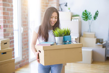 Young Beautiful Woman Moving Cardboard Boxes At New Home