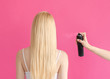 Leinwanddruck Bild - Hairstyle Concept photo in back view Woman's hand is spraying fixative spray on strands of a long-haired blonde girl against pink background