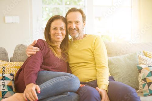 Fotografia  Middle age romantic couple sitting on the sofa at home