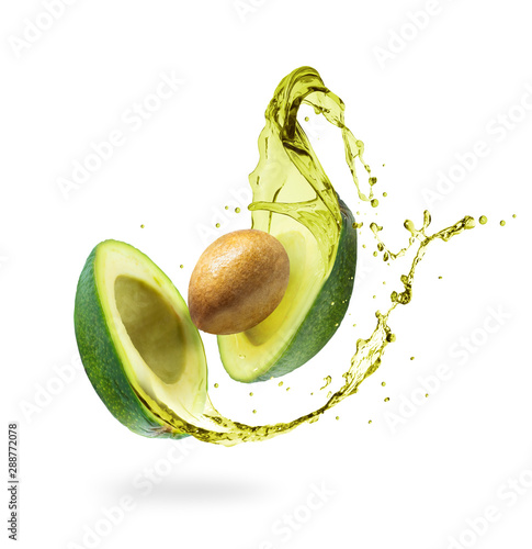 Valokuvatapetti Sliced avocado with splashes isolated on white background