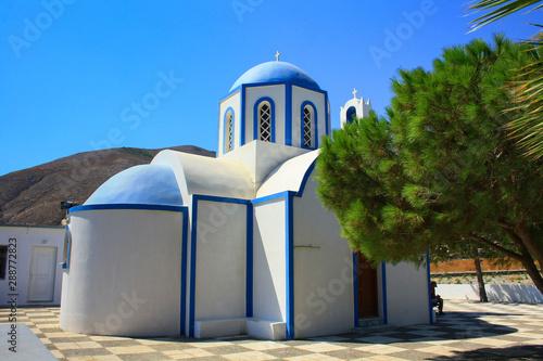 Piękny biało-niebieski kościół na tle wzgórz, Santorini, Grecja - fototapety na wymiar