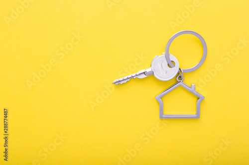 Fototapeta House keys with trinket on color background, top view with copy space. obraz