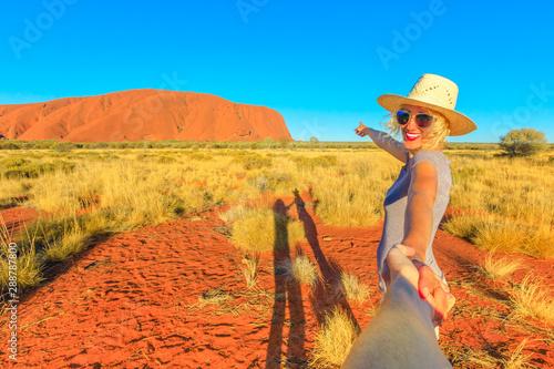 Follow me, smiling girl with hat holding hands at Uluru-Kata Tjuta National Park, Northern Territory, Australia Fotobehang