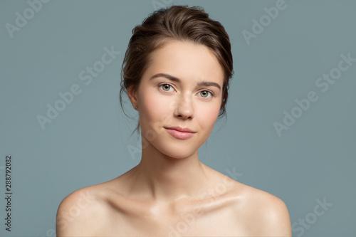 Fotografiet  Portrait of beautiful woman. Perfect skin. Blue background.