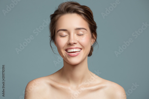 Portrait of smiling beautiful woman. Perfect skin. Blue background.