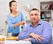 Leinwandbild Motiv Wife threatens the finger of her husband at kitchen