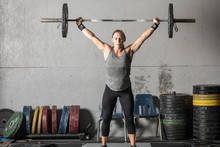 Strong Young Woman With Heavy Barbell Over Her Head In Grungy Gym.