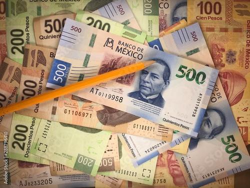 Fotomural  Mexican pesos bills spread randomly over a flat surface with a pencil on top