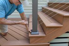 Builder Installing Railing On New Deck