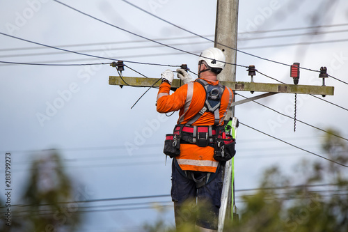 Fototapeta A linesman with a power company connects a new house in a rural area to the main network obraz