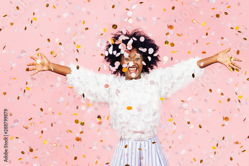 Foto Happy young woman celebrating with arms out and lots of falling confetti