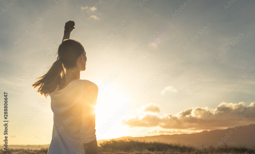 Fototapeta Young female outdoors with fist in the air feeling strong and confident. Victory and success concept.