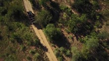Drone Shot Of A Safari Game Drive Vehicle With Guests Driving Up A Winding Dirt Road In An African Game Reserve
