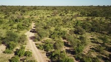 Tracking Wide Drone Shot Of A Safari Game Drive Vehicle With Guests Driving Up A Dirt Road Showing The Wide Open African Landscape