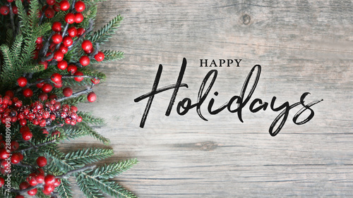 Obraz Happy Holidays Text with Holiday Evergreen Branches and Berries Over Rustic Wooden Background - fototapety do salonu