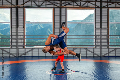 Photo A  wrestler boy in a sports tights wrestles with an adult male wrestler on a wrestling carpet in the gym