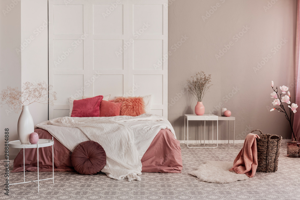 Fototapeta Amaranth pillow and dirty orange bedding on king size bed in fashionable bedroom interior