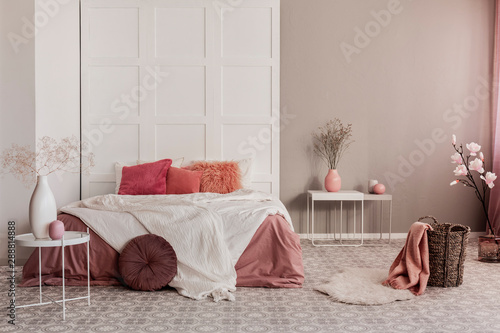 Photo Amaranth pillow and dirty orange bedding on king size bed in fashionable bedroom