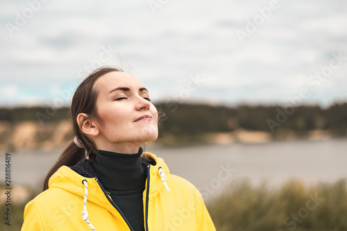 Obraz na plátně  Portrait of a young woman in nature in a yellow jacket breathing fresh clean coo