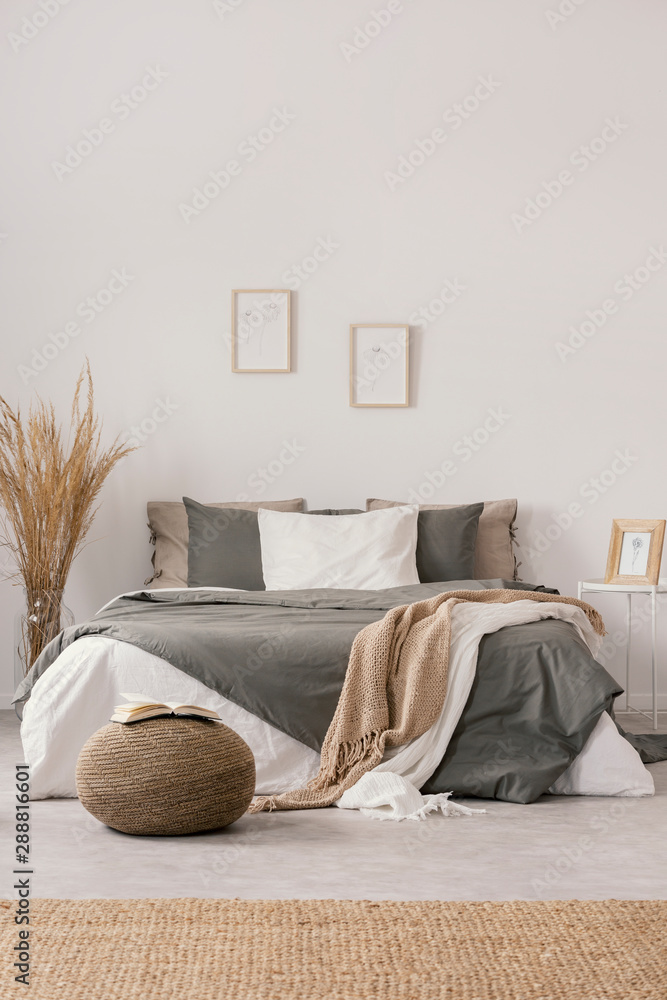 Fototapeta White and beige blankets on grey duvet on comfortable bed in bright bedroom interior
