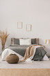 canvas print picture - White and beige blankets on grey duvet on comfortable bed in bright bedroom interior