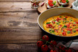 omelette with vegetables and cherry tomatoes on dark wooden background with copy space