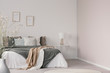 Leinwandbild Motiv White and beige blankets on grey duvet on comfortable bed in bright bedroom interior
