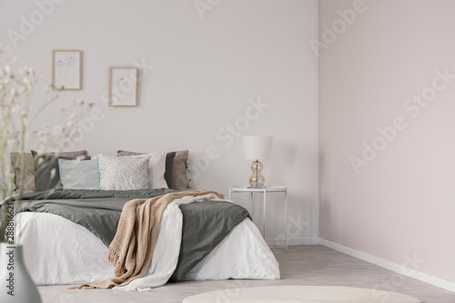 Obraz White and beige blankets on grey duvet on comfortable bed in bright bedroom interior - fototapety do salonu