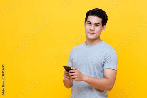 Pinturas sobre lienzo  Young good looking Asian man in casual style holding a smartphone