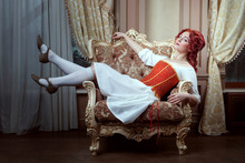 Portrait Of A Beautiful Young Woman In A Dress And Corset. Woman Is Lying On An Armchair.