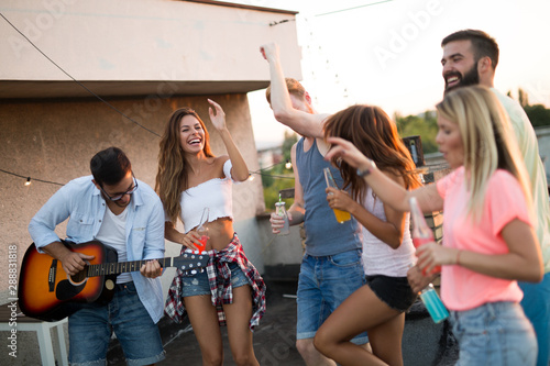 Group of carefree friends dancing have fun in summer