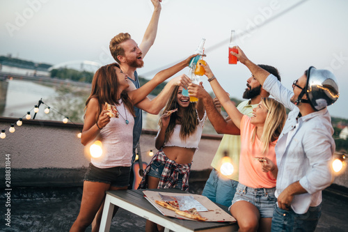 Group of young people having fun at a summertime party, at sunset