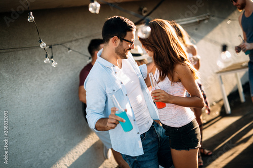 Happy young dancing couple having fun and enjoying party at summer