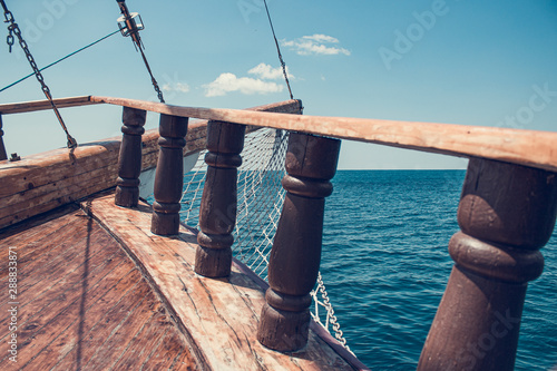Foto op Plexiglas Schip The bow of an ancient ship. Vintage ship at sea. View of the sea through the beams and the side of an old wooden ship, rapidly sailing on the sea