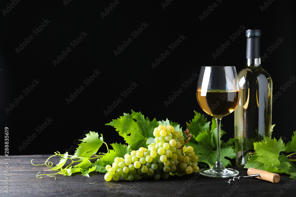 Fototapeta Fresh ripe juicy grapes with wineglass on grey table against black background, space for text