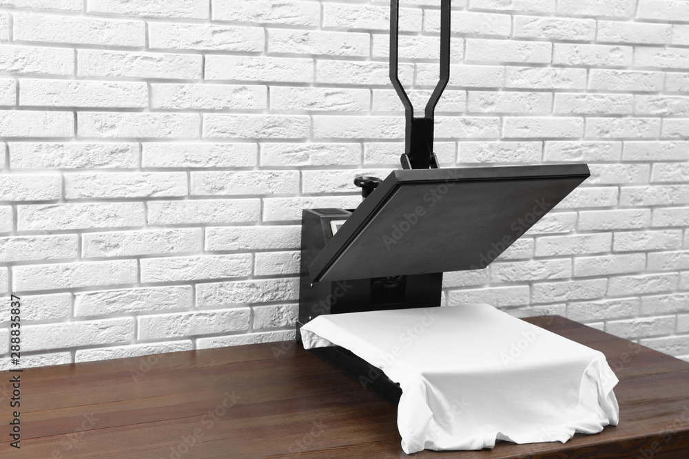 Fototapeta Heat press machine with t-shirt on wooden table near white brick wall. Space for text