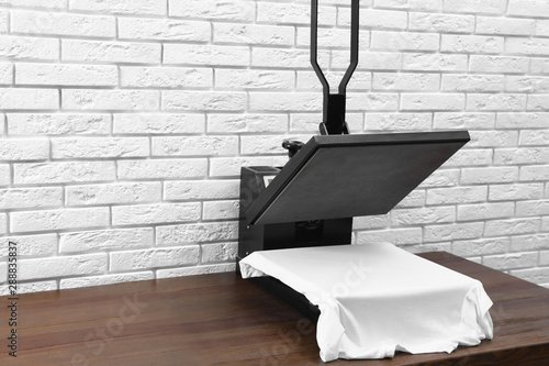 Heat press machine with t-shirt on wooden table near white brick wall Canvas Print