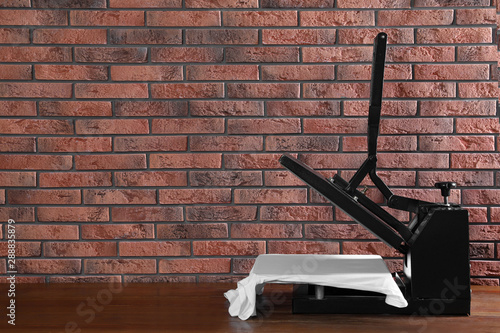 Pinturas sobre lienzo  Heat press machine with t-shirt on wooden table near brick wall, space for text