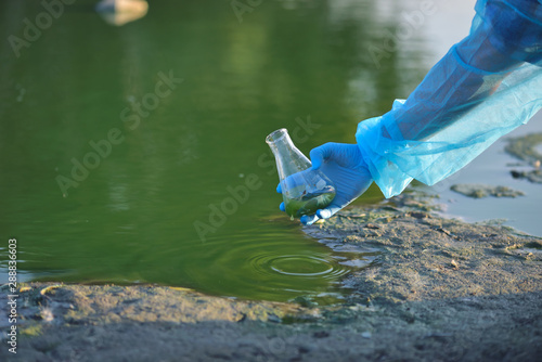 Valokuva  Close-up environmentalist hand of a researcher in a process of taking a sample o