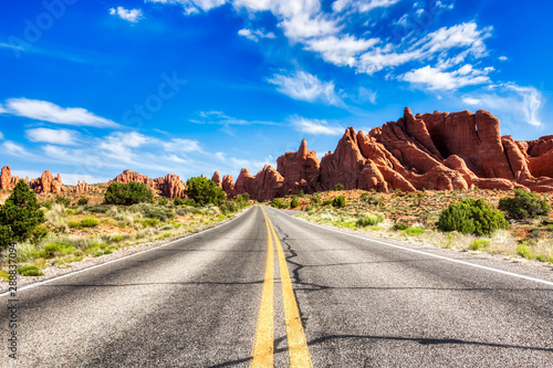 Papiers peints Route 66 Driving through the-Desert with Monument Rock along the Road During Sunny Day, Arches NP
