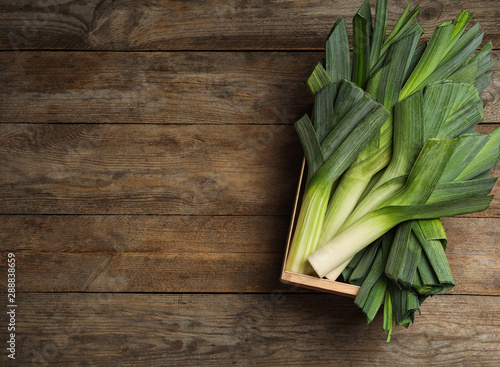 Fototapeta Crate of fresh raw leeks on wooden table, top view with space for text. Ripe onion obraz