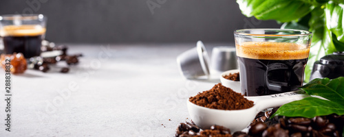 Background with glass cup of coffee, coffee beans and leafs. Beverage cafe shop concept with copy space.
