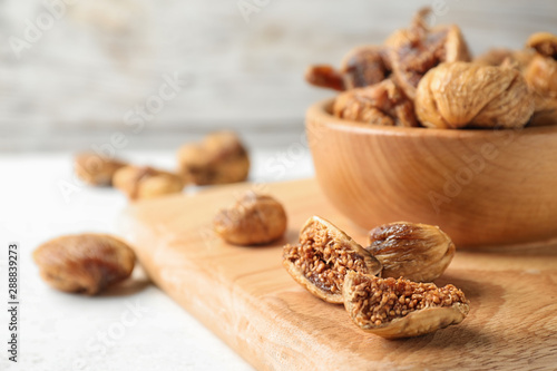 Fotomural  Wooden board with tasty dried figs on light table. Space for text