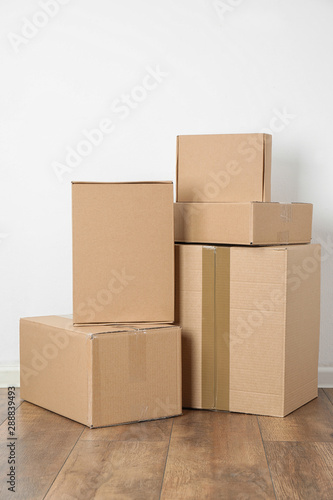 Pile of cardboard boxes near white wall indoors