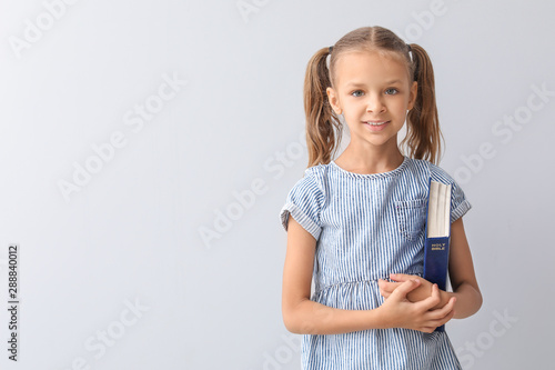 Photo Cute little girl with Bible on light background