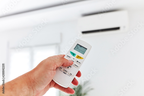 Photo Modern air conditioner unit with a hand holding a remote.