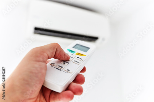 Modern air conditioner unit with a hand holding a remote. Canvas Print